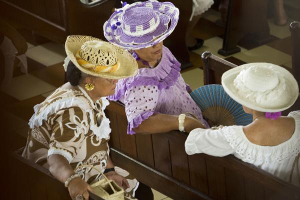 Dames Tahitiennes en tenue colorée discutant sur les bancs de l'Eglise