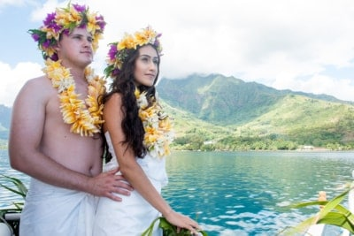 Couple wearing polynesian weeding pareos and flowers