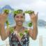 Jolie tahitienne qui accueille un touriste avec une couronne de fleurs